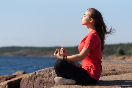18's: Young Woman sitting in lotus position on rock by the sea Stock Photo