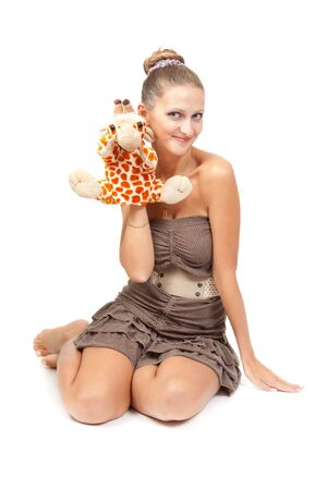 Portrait of beautiful girl sitting on the floor in the studio with plush toy in the shape of a giraffe. isolate on white background. photo