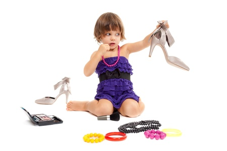 Cute little girl with cosmetics and womens shoes in the studio. Isolate on white.