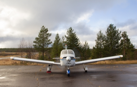 fixed wing aircraft: small aircraft parking stands at the airfield in the forest ready to go. Front view. Stock Photo