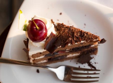 rebanada de pastel: pastel de chocolate con cerezas en un plato blanco con un tenedor Foto de archivo