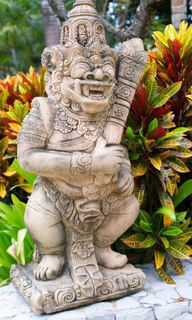 Thai stone god in the bushes of tropical plants. Short depth of field. photo