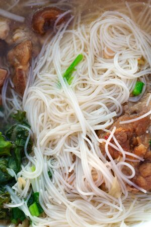 Thai soup with noodles and meat close up photo