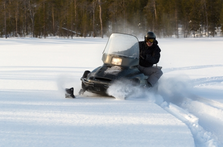 man riding a snowmobile on a background of forest