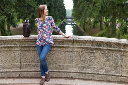 19's: Beautiful young girl on the old stone bridge in the coniferous forest