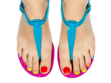 human toe: Female legs in summer shoes with a colored pedicure. Isolated on white