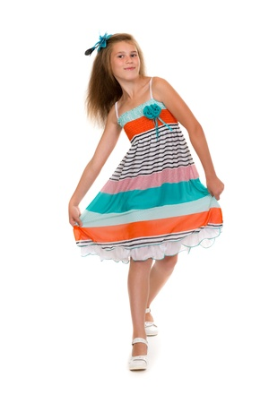 11 year old girl dances in colorful dress in the studio. Isolate on white. photo