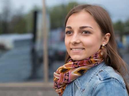 19's: portrait of a beautiful girl in a denim jacket with a scarf on the street