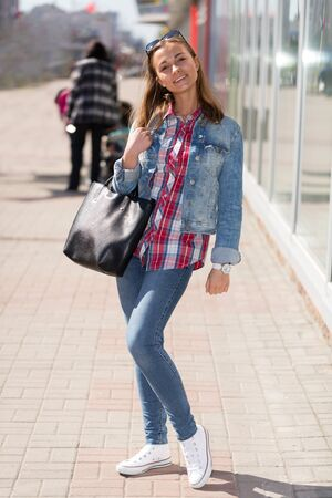 19's: portrait of a girl in full growth in jeans on the street Stock Photo