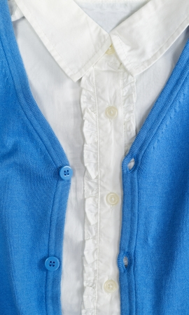 Trendy blue cardigan with a white shirt closeup photo