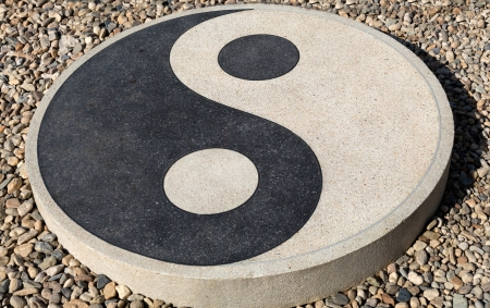 Yin yang sign on a stone on the shingle photo
