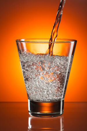 In the glass of mineral water are poured. Against a bright orange light spot with a smooth gradient. photo