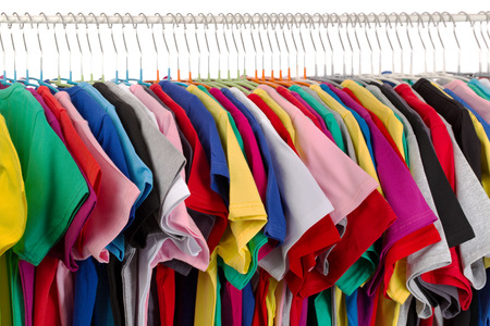 Rack of assorted colored T-shirts. Isolate on white.