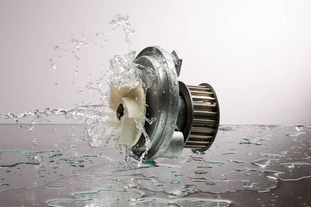 Auto parts, engine cooling pump in water splash on gray gradient background photo