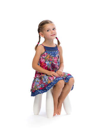 Little girl in a colored dress on a chair in the studio and shy, isolate on white.