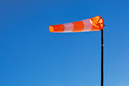Orange and white windsock blows against a blue sky. photo