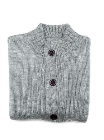 Grey knit sweaters folded on white background. photo