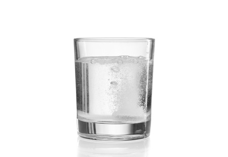 Glass with efervescent tablet in water. Isolated on white. photo