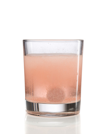 fizzy tablet: Orange effervescent tablet in a glass of water. Isolate on white.