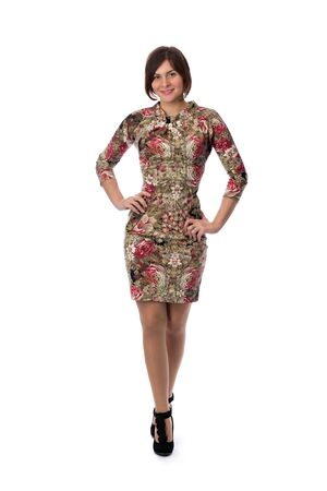 full height: Beautiful slim girl in a dress with a pattern to his full height. Studio, isolate on white.