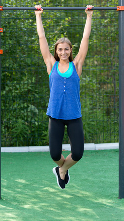 outdoor exercise: Young athletic girl hanging on horizontal bar