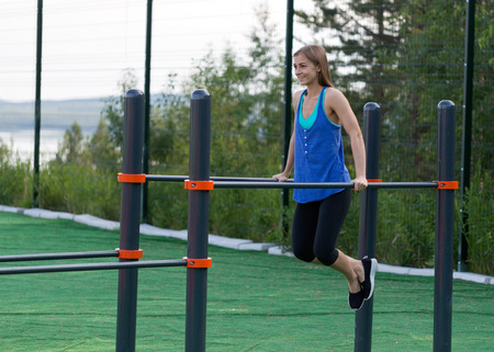 pushed: Beautiful girl in sportswear is pushed on bars. Stock Photo