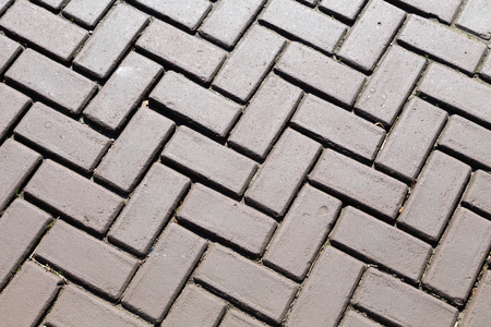 superficial: Dark gray brick pavers. Background.