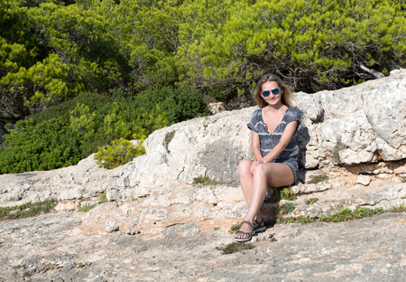 Beautiful girl sits on a rock in a forest, Mallorca, Spain
