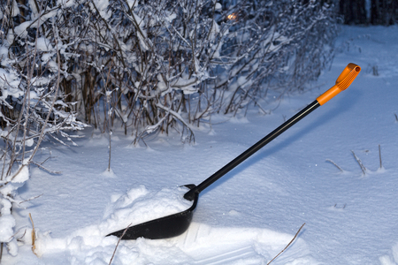 Shovel in the snow in the night forest Stock Photo