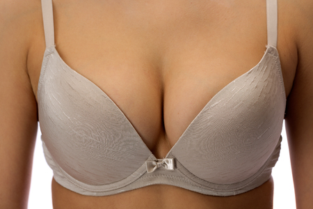 Female breast in a beige bra closeup. Isolate on white background