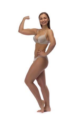 Girl in swimsuit showing biceps. Isolate on white background photo
