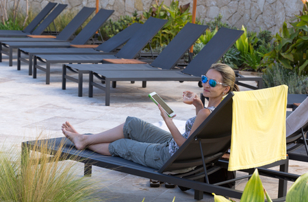 Girl in sunglasses on a lounger with a cocktail and a tablet photo