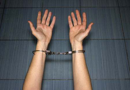 sadism: police handcuffs on the hands of women criminals and crimes Stock Photo