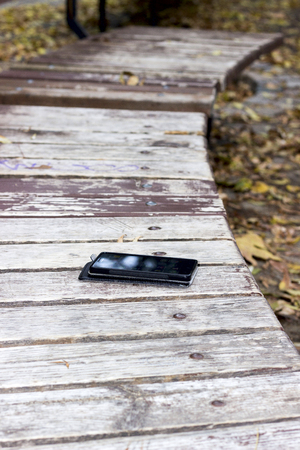 forgot smartphone in a city park is on the bench Stock Photo