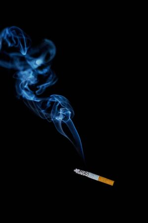 harmful to the environment: smokes a cigarette on a black background, is harmful to health Stock Photo