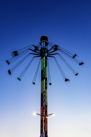 an attraction in an amusement park against the background of an evening sky