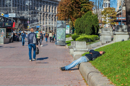 alcoholism and drug addiction in the city a drunk person is lying on the grass.Ukraine. Kiev 06.11.2018