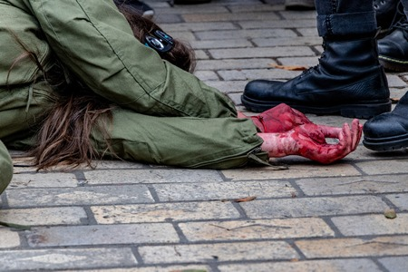 violence against people battered womans hands in the blood next to a man in military shoes.