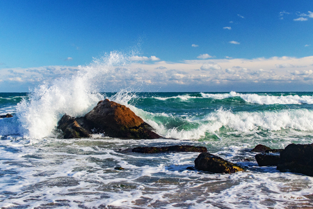 storm at sea, splashing waves and rocks on the shore