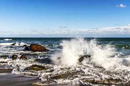 storm at sea waves break on the stones splashing water