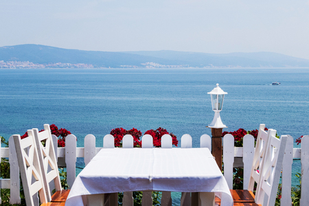 romantic dinner white tablecloth white chairs on the background of the sea .
