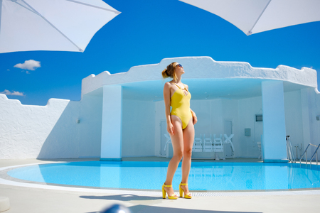 girl in a bathing suit by the pool in the summer sun rest