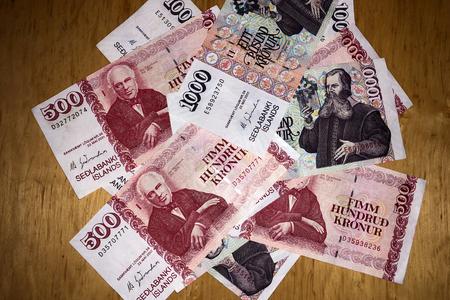 Icelandic cash. Money of Iceland. Several Icelandic krona bills on wooden table. Icelandic krona is the national currency of Iceland (kronur) Imagens