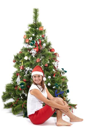 Beautiful smiling woman in Santa cap next to the Christmas tree, isolated on white