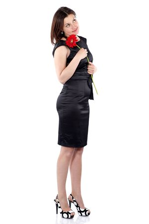 Beautiful young woman in black dress holds gerbera flower in hands, turned the right side and looks up