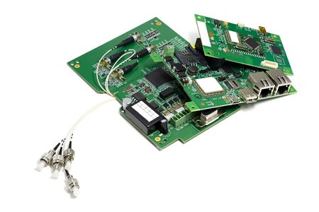 Set of electronic printed circuit boards with optic connectors attached and other components, angled view, isolated on white