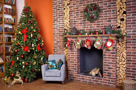 Christmas tree in the room near the fireplace and home library, the Christmas mood with gifts Standard-Bild