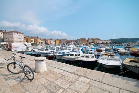The bike is parked on the pier in port of Rovinj, Croatia. Yachts landing, motorboats and boats on water, medieval vintage houses of old town on the background. Фото со стока