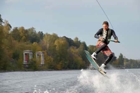 Moscow, Russia - September 28, 2008: Wakeboarding rider showing tricks and skills at free ride on the city river. Wakeboarder behind the motorboat