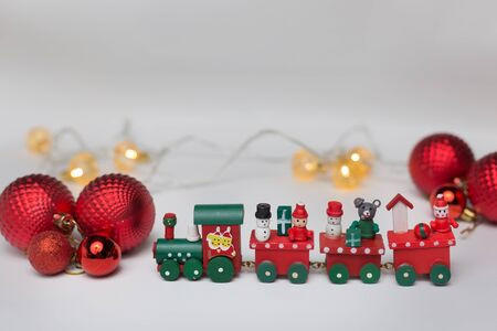 Backgrounds and textures. Toy train on a white background with red balls and a shiny garland